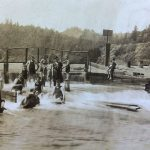 Vintage photo of early 20th century russian river residents splashing at the river