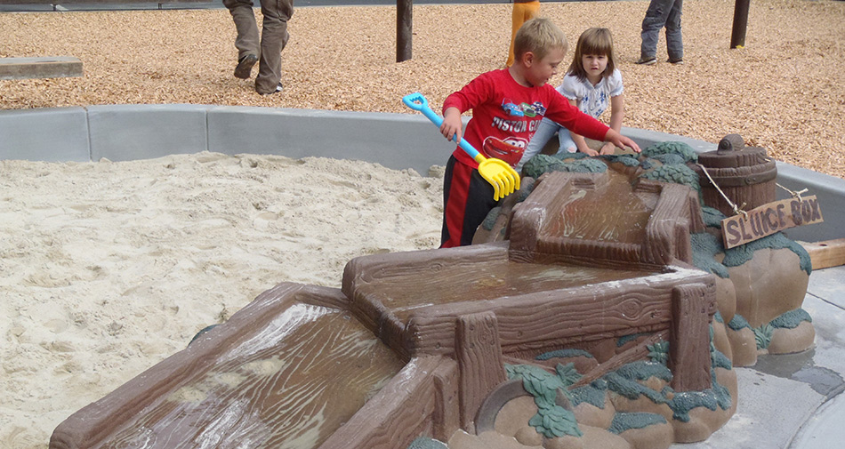 Kids enjoying the sandpit sluice at J.K.Wright Playground